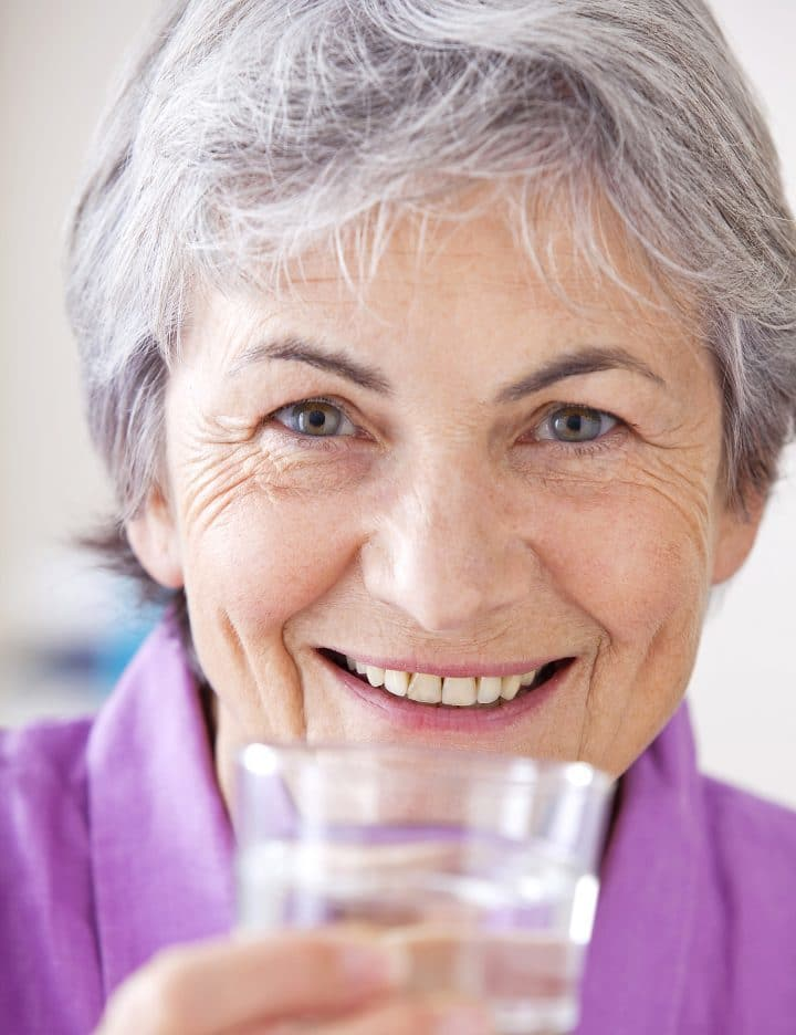 Grey Haired Woman With Glass Of Water